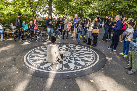john lennon: New York, USA - OCT 21, 2015: people having their picture taken on the IMAGINE mosaic in Strawberry Fields Central Park in Manhattan. People come all day to this John Lennon memorial.