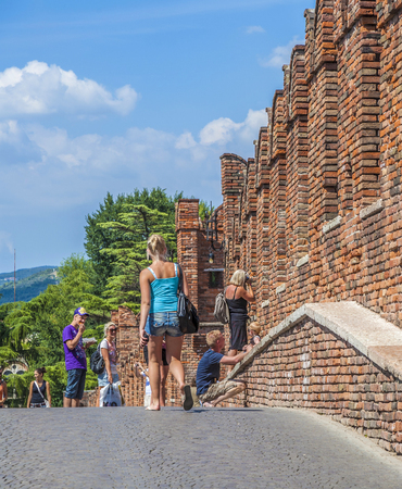 VERONA, ITALY - AUG 5, 2009: people visit Castelvecchio in Verona, Italy. The castle stands on the probable location of a Roman fortress outside the Roman city and was built in 1354.