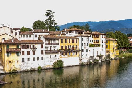 grappa: facade of houses at river brenta with romantic village Basano del Grappa
