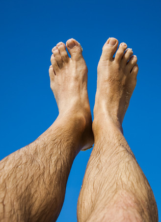 fine legs: leg and feet of a man in front of the clear blue sky