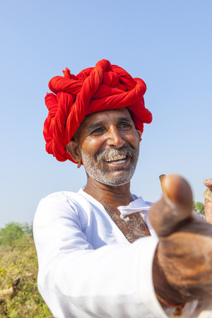 rajasthani: PUSHKAR, INDIA - OCTOBER 22: A Rajasthani tribal man wearing traditional colorful turban and loves to pose  at the annual Pushkar Cattle Fair on October 22, 2012 in Pushkar, Rajasthan, India. Editorial
