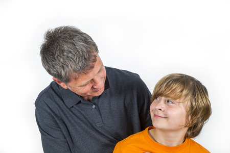 smooching: father and cute smiling son hugging the other Stock Photo