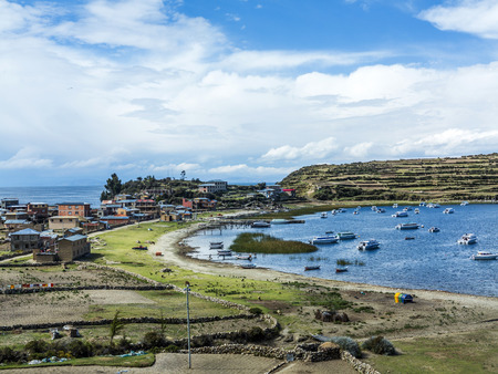terracing: view to Titicaca lake at  Isla del Sol with small village Yumani under blue sky