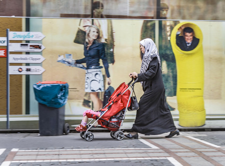 stranger: FRANKFURT, GERMANY - MAY 23, 2008: islamic woman with her child in a buggy in Frankfurt, Germany. She walks along the famous shopping Mile Zeil.