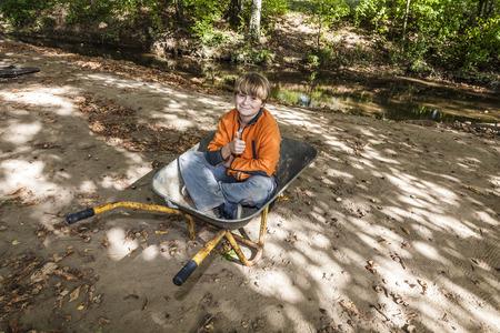 carretilla de mano: niño lindo se sienta en la carretilla y se relaja