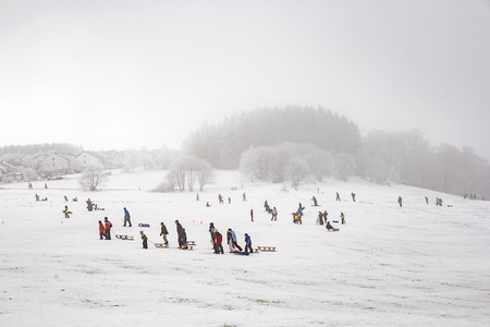 sledging people: OBERREIFENBERG, GERMANY - JAN 16, 2010: children are skating at a toboggan run in winter on snow. Snow in this area is very seldom due to world wide encrease of temperature.