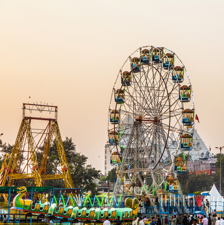 poorer: DELHI, INDIA - NOV 11, 2011: people enjoy the big wheel in the amusement park in Delhi, India in front of the red fort. The prices are very low to enable poorer people a ride. Editorial