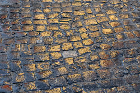 cobblestones: wet cobblestones reflect the sun in sunset