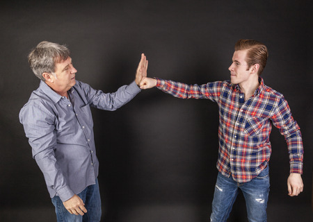 lean back: father and son lean on back to back isolated on black Stock Photo