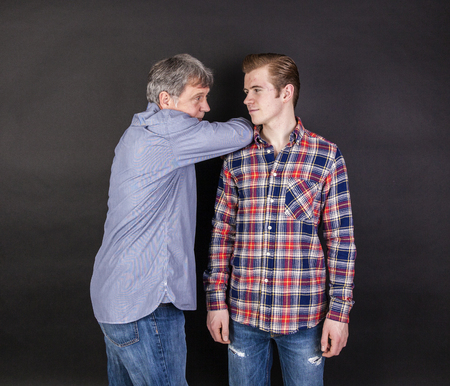 trustful: father and son lean on back to back isolated on black Stock Photo