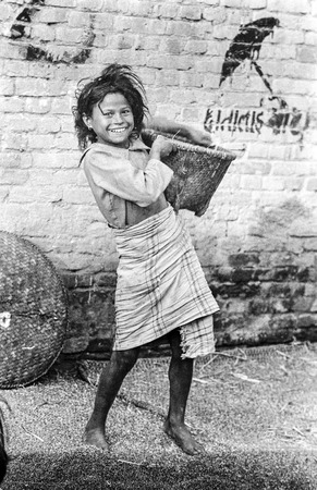 threshing: BHAKTAPUR, NEPAL - JUL 4, 1981: young nepalese girl carries corn from threshing in her basket and smiles. Hand threshing is the common way in Nepal to handle the harvest.
