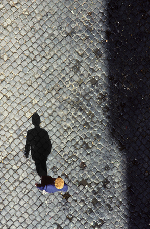 lonelyness: old man from birds view walking on cobble stone in Lisbon