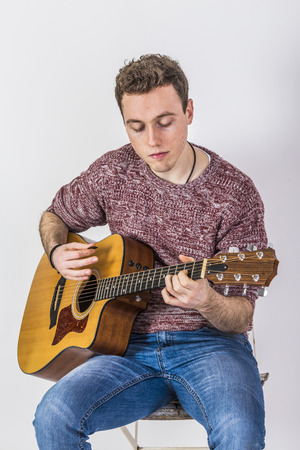 sits on a chair: teenage guitar player sits on a chair and plays guitar Stock Photo