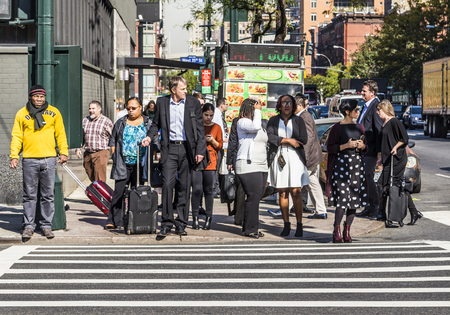 red traffic light: NEW YORK CITY, USA - OCT 21, 2015: people near Wall street in Manhattan wait at red traffic light for crossing the street in New York, USA.