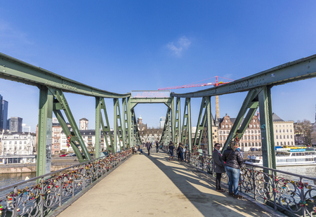 foot bridges: FRANKFURT AM MAIN, GERMANY - FEB 28, 2015: people at famous Eiserner steg with love locks over the river Main. The Eiserner Steg is a pedestrian bridge only built in 1868.