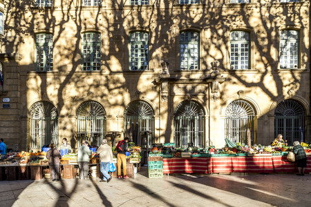 common market: AIX EN PROVENCE, FRANCE - DEC 10, 2015: local people buy fresh vegetables and fruits at the local market in Aix en Provence, France. Spending money for fresh food is very common in France.