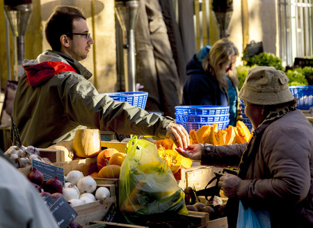 spending money: AIX EN PROVENCE, FRANCE - DEC 10, 2015: local people buy fresh vegetables and fruits at the local market in Aix en Provence, France. Spending money for fresh food is very common in France.