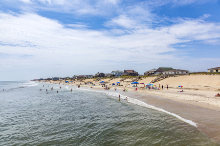 nags: NAGS HEAD, USA - JUL 18, 2010: people enjoy bathing  in Nags Head, USA. Established in the 1830s as first tourist colony. The first oceanfront cottage was built here around 1855 by Dr. W.G. Pool.