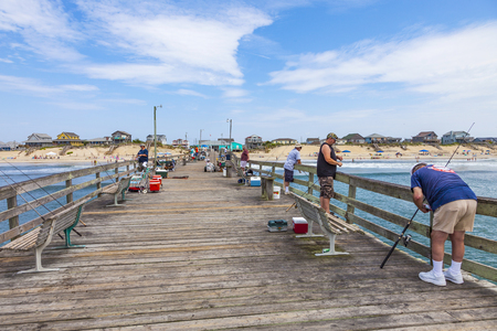 oceanfront: NAGS HEAD, USA - JUL 18, 2010: people enjoy fishing at the famous pier in Nags Head, USA. The first oceanfront cottage was built here around 1855 by Dr. W.G. Pool and the lenght of the pier is 750 ft.