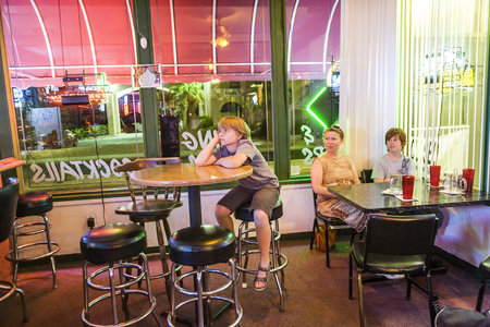 enjoys: LAKE HAVASU, USA - JULY 8, 2008: family enjoys the typical pizza restaurant and Bar in Lake Havasu and watches TV while dining. The bar is illuminated with neon lights. Editorial