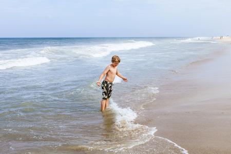 boy has fun standing in the ocean in the stormy beach