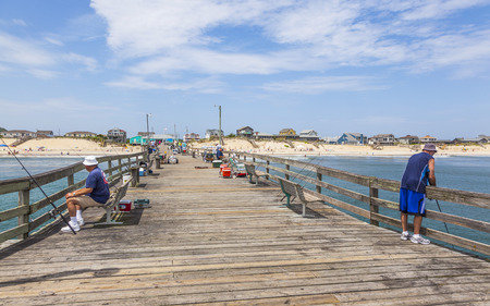 nags: NAGS HEAD, USA - JUL 18, 2010: people enjoy fishing at the famous pier in Nags Head, USA. The first oceanfront cottage was built here around 1855 by Dr. W.G. Pool and the lenght of the pier is 750 ft.