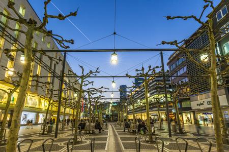 walking zone: FRANKFURT, GERMANY - MAR 18, 2016: people walk along the Zeil in the evening in Frankfurt. The Zeil is since changing to pedestrian zone in 1970 Germanys most popular pedestrian Zone.
