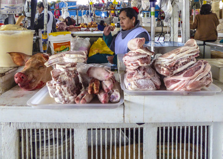 indios: CUZCO, PERU - JAN 18, 2015: local people sell meat and vegetables at the indoor market in Cuzco, Peru. Farmers from the Cuzco area go here to sell their goods. Editorial
