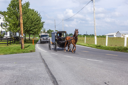 amish buggy: LANCASTER, USA - JULY 13, 2010: amish people ride in their horse carts in Lancaster, USA. Amish people dont use electricity as well as cars. They life the traditional way of the 17th century.