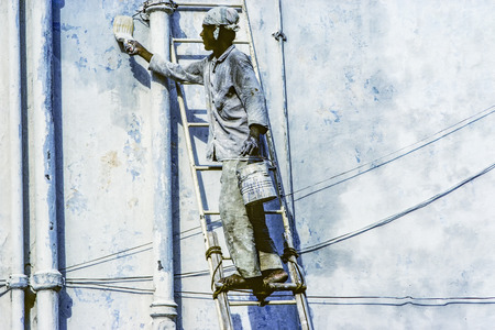 self made: JAISALMER, INDIA - AUG 6, 1994: local painter paints the old wall in the typical blue color in Jaisalmer, India. The ladder is self made by wooden sticks.