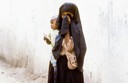 illiteracy: HADHRAMAUT, YEMEN - JULY 4, 1991: arabic unknown mother carries her baby in a  wraparound garment  in Hadhramaut, Yemen. in 2008 still 62 percent of women in rural areas are  illiteracy.