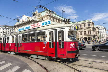 streetcar: VIENNA, AUSTRIA - APR 24, 2015: people in streetcar in front of Vienna State Opera house - the Hofburg - with history dating back to mid-19th century. It is located in centre of Vienna
