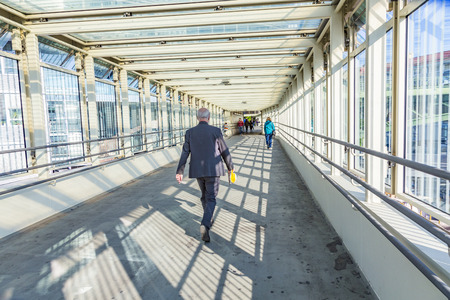 pedestrian bridge: VIENNA, AUSTRIA - APR 24, 2015: people use the pedestrian bridge to cross the street at Althangrund in Vienna. Vienna offers a lot of modern architecture in combination with old buildings.