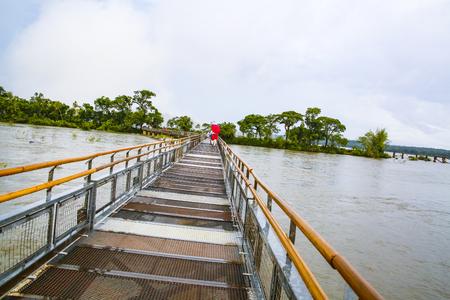 tropica: bridge over the River Iguacu in Brazil with cloudy sky