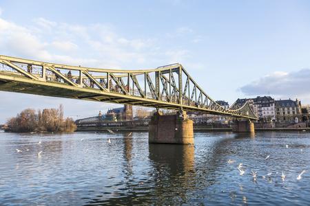 river main: FRANKFURT, GERMANY - FEB 22, 2015: people at the Eiserner Steg - old iron bridge over the river Main in Frankfurt. The Eiserner Steg is a pedestrian bridge built in 1868.