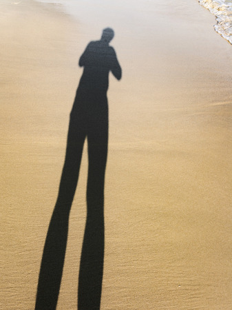adult footprint: long body shadow of a man in the fine sand of the beach, feet is visible
