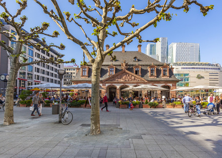 paveway: FRANKFURT, GERMANY- MAY  6, 2016: people enjoy the sunny day at cafe Hauptwache  in Frankfurt, Germany. The baroque building Hauptwache was built in 1730 as a police station and serves nowadays as a cafe.