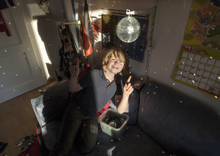 mirror ball: happy boy enjoys sitting im his nursery with operting mirror ball Stock Photo