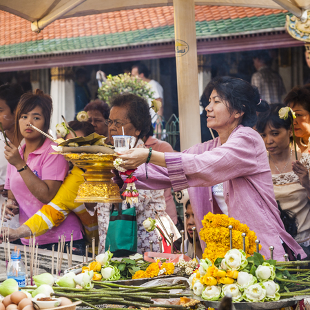 thai believe: BANGKOK, THAILAND - JAN 4, 2010: people enjoy offerings at the grand palace in Bangkok, Thailand. Thai people strongly believe in Buddhism and offerings is part of daily life. Editorial