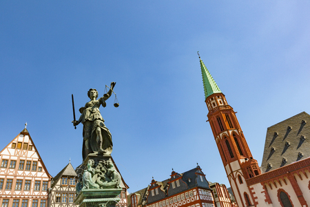 justitia: Justitia - Lady Justice - sculpture on the Roemerberg square in Frankfurt, built 1887 with roof of church Stock Photo
