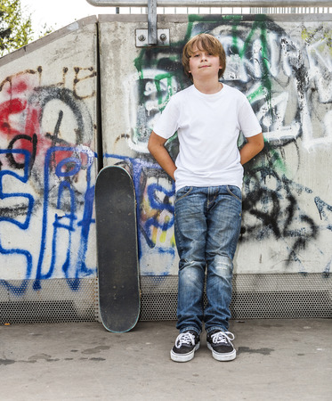 skate board: young boy relaxes with his skate board at the skate park