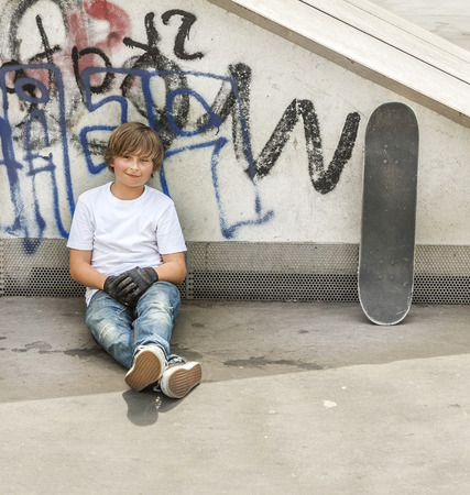 skate park: young boy relaxes with his skate board at the skate park