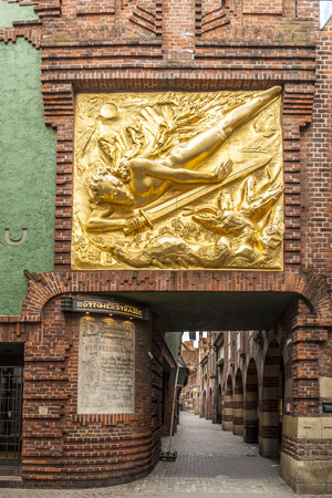to paula: BREMEN, GERMANY - MAY 12, 2016: Boettcherstreet  with golden der Lichtbringer in Bremen. Only about 100 m long, it is famous for its unusual architecture and ranks among the citys main cultural landmarks. Editorial
