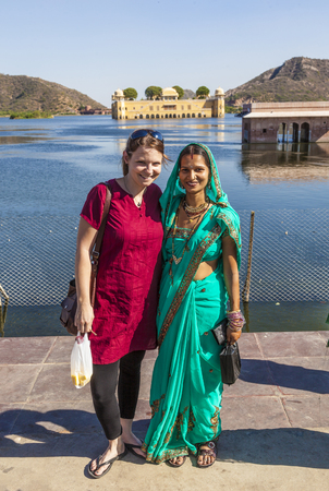 sagar: JAIPUR, INDIA - NOVEMBER 21, 2011 : Portrait of Indian and western girl in colorful ethnic attire at Sagar Lake in Jaipur. The lake with water palace is a spot for indian tourists.