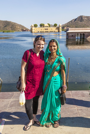ethnic attire: JAIPUR, INDIA - NOVEMBER 21, 2011 : Portrait of Indian and western girl in colorful ethnic attire at Sagar Lake in Jaipur. The lake with water palace is a spot for indian tourists.