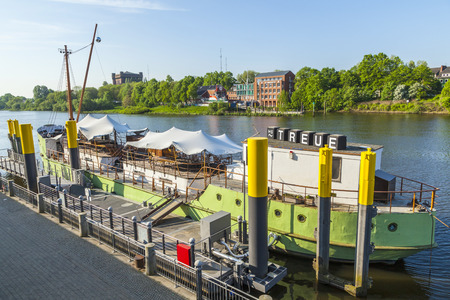 ms: BREMEN, GERMANY - MAY 12, 2016: River Weser with ship MS Treue anchored at river bank. The MS Treue can be hired for partys and is the club ship of Bremen.