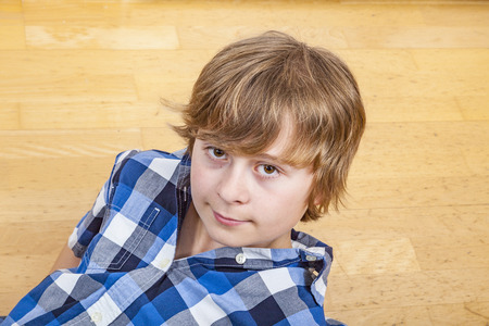 only one teenage boy: cute young boy lying at the wooden floor Stock Photo
