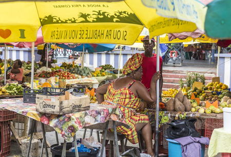 the place is outdoor: POINTE-A-PITRE, GUADELOUPE - MAY 17, 2015: woman sells fresh fruits at the outdoor market in Guadeloupe. The Pointe-a-Pitre Market is located by the harbour next to Place de la Victoire.