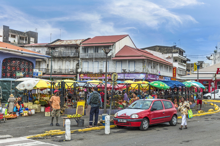 the place is outdoor: POINTE-A-PITRE, GUADELOUPE - MAY 17, 2015: people at the outdoor market in Guadeloupe. The Pointe-a-Pitre Market is located by the harbour next to Place de la Victoire.