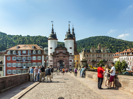 HEIDELBERG, GERMANY - JULY 7, 2013: people visit old bridge and town gate  in Heidelberg, Germany. The real name of the Old Bridge is Karl-Theodor-Bruecke. It was completed in 1788.